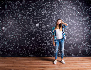 Student holding her head, thinking, against big blackboard with mathematical symbols and formulas. Studio shot on black background.