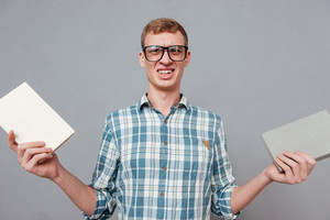 Student in glasses with books in studio. looking at camera. isolated gray background