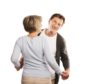 Studio portrait of happy seniors couple dancing. Isolated on white background.