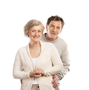 Studio portrait of happy seniors couple hugging. Isolated on white background.