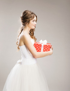 Studio portraits of beautiful bride with gift isolated on gray background