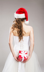 Studio portraits with beautiful bride isolated on gray background. She is holding christmas gift.