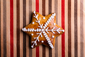 Studio shot of gingerbread star on striped wrapping paper