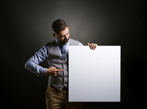 Studio shot of modern hipster businessman holding blank advertisement on black background