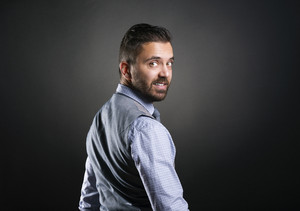 Studio shot of modern hipster businessman, isolated on black background