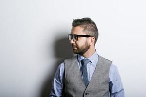Studio shot of modern hipster businessman leaning against wall