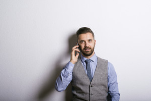 Studio shot of modern hipster businessman making a phone call with mobile phone