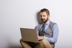 Studio shot of modern hipster businessman using laptop