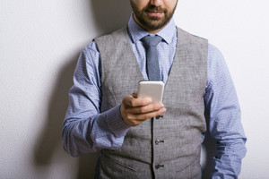 Studio shot of modern hipster businessman using mobile phone