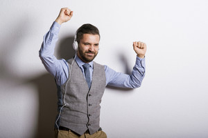 Studio shot of modern hipster businessman with headphones, listening to music and dancing