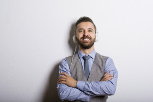 Studio shot of modern hipster businessman with headphones, listening to music