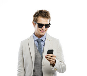 Studio shot of young modern businessman in sunglasses with mobile phone