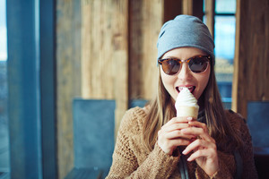 Stylish girl eating ice-cream in cafe