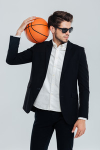 Stylish handsome man in black suit and sunglasses holding basket ball on his shoulder over grey background