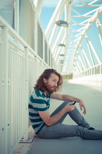 stylish hipster model with long red hair and beard lifestyle on the phone in the street