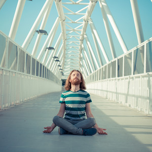 stylish hipster model with long red hair and beard yoga in the street