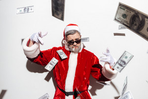 Stylish santa claus in sunglasses smoking and throwing money in the air