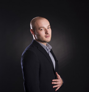 Successful business man is posing in studio isolated over black background