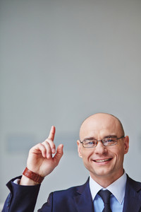 Successful businessman in eyeglasses pointing upwards