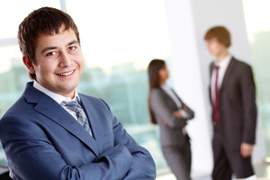 Successful businessman looking at camera with interacting colleagues on background