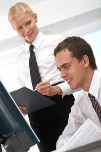 Successful businessman looking at monitor of computer with secretary near by