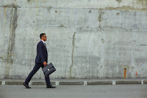 Successful businessman with briefcase walking along concrete wall