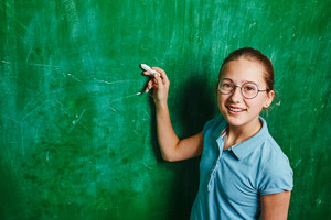 Successful schoolgirl looking at camera while explaining idea on blackboard