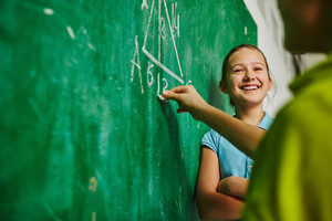 Successful schoolgirl looking at classmate while he explaining geometric task on blackboard