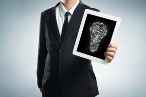 successful young businessman shows the screen of the tablet with bright idea