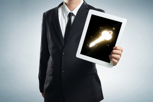 successful young businessman shows the screen of the tablet with key to success symbo
