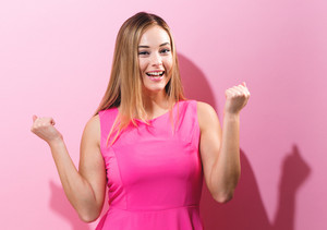 Successful young woman on a pink background