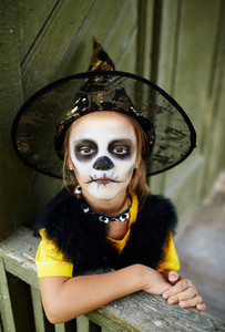 Sullen girl in Halloween costume looking at camera