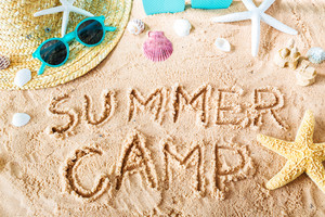 Summer Camp text in the sand with beach accessories