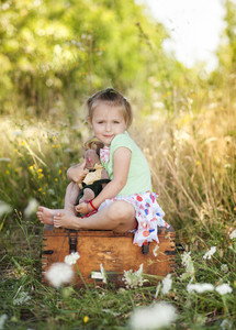 Summer outdoor portrait of cute little girl sitting on meadow with old suitcase with toys