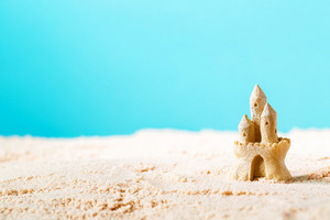 Summer theme with sand castle on a bright blue background