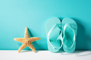 Summer theme with sandals and starfish on a bright blue background
