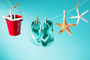 Summer theme with sandals, pail and starfish on a bright blue background