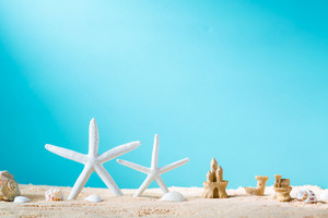 Summer theme with starfish and sand castle in the sand