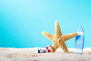 Summer theme with starfish and surfboard in the sand on a bright blue background