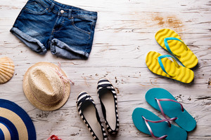 Summer vacation composition. Denim shorts, hats, espandrilles and flip flops against white wooden background. Studio shot, flat lay.