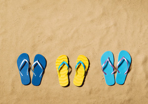 Summer vacation composition. Three pairs of flip flop sandals on a beach. Sand background, studio shot, flat lay. Copy space.