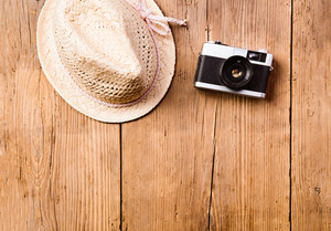 Summer vacation composition. Wicker hat and vintage camera against wooden background. Studio shot, flat lay. Copy space.