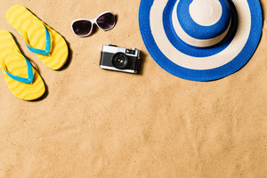 Summer vacation composition with a pair of yellow flip flop sandals, hat, sunglasses and retro styled camera laid on a beach. Sand background, studio shot, flat lay. Copy space.