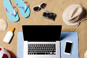 Summer vacation composition with laptop, smart phone, a pair of blue flip flop sandals, hat, sunglasses, sun screen and other stuff on a beach. Sand background, studio shot, flat lay, copy space.