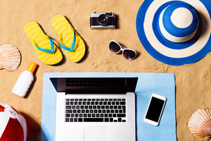 Summer vacation composition with laptop, smart phone, a pair of yellow flip flop sandals, hat, sunglasses, sun screen and other stuff on a beach. Sand background, studio shot, flat lay, copy space.