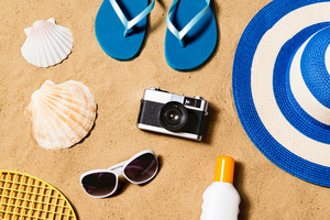 Summer vacation composition with pair of blue flip flop sandals, hat, sunglasses, sun cream and other stuff on a beach. Sand background, studio shot, flat lay.