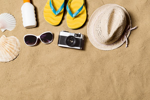 Summer vacation composition with pair of yellow flip flop sandals, hat, sunglasses, sun cream and other stuff on a beach. Sand background, studio shot, flat lay. Copy space.