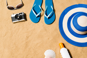 Summer vacation composition with pair of yellow flip flop sandals, hat, sunglasses, sun cream and wintage camera on a beach. Sand background, studio shot, flat lay. Copy space.