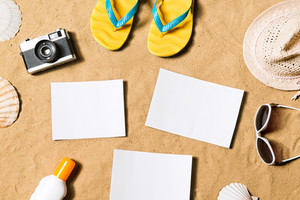 Summer vacation composition with pair of yellow flip flop sandals, hat, sunglasses, sun cream, empty paper sheets and other stuff on a beach. Sand background, studio shot, flat lay. Copy space.