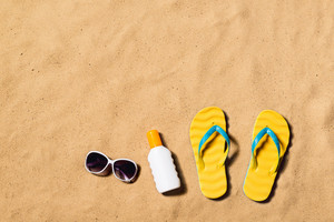 Summer vacation composition with pair of yellow flip flop sandals, sunglasses and sun cream on a beach. Sand background, studio shot, flat lay. Copy space.